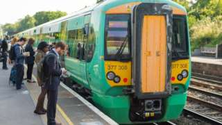 Commuters queue to get on a Southern train