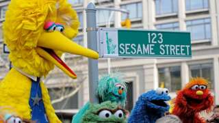 Big Bird (L) and other Sesame Street puppet characters pose next to temporary street sign November 9, 2009
