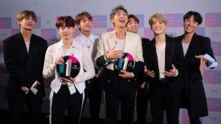BTS smiling holding awards