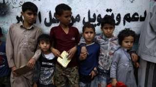 Children queue for aid in Sanaa, Yemen