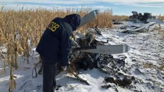 An investigator looks at wreckage of plane in the snow