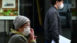 A woman wearing a face mask, amid concerns of the COVID-19 coronavirus, touches her face on a street in Tokyo on April 6, 2020.