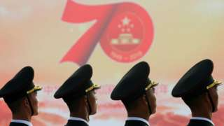 """Soldiers of People""""s Liberation Army (PLA) are seen in front of a sign marking the 70th founding anniversary of People""""s Republic of China before a military parade on its National Day in Beijing, China October 1, 2019."""