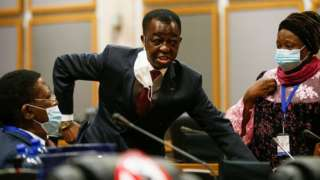Roger Nkodo Dang (C) speaks with others inside the house following its postponement in Midrand, Johannesburg on June 1, 2021