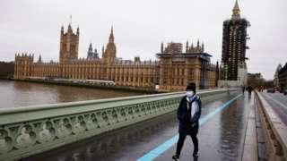 A woman wearing a face mask walks across Westminster Bridge
