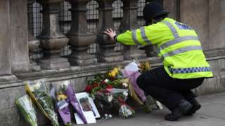 A policeman laying flowers in tribute to PC Keith Palmer