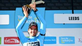 Greg van Avermaent holds up a Y shaped gold trophy to celebrate winning the 2018 Tour de Yorkshire