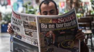 """A man reads a newspaper with a headline concerning diplomatic tensions between Turkey and The Netherlands, which translates as """"What a Barbarism"""" in Istanbul on March 13, 2017."""