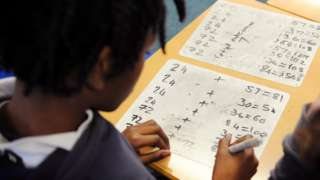 Pupil filling out arithmetic work at school