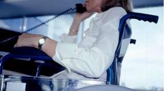 Woman in wheelchair uses landline