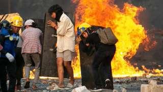 Protestors behind shields on burning street in Myanmar.