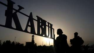 Silhouettes of people outside a sign for Kabul
