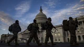 National Guard troops march past the US Capitol building as day breaks in Washington, DC, USA, 14 January 2021