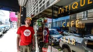 Guto Lima em frente a fachada de sua loja, com vidro escrito 'Antique Café'