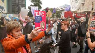 An anti-abortion supporter holds up leaflets as pro-choice demonstrators march in Belfast