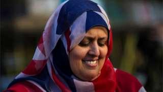 امراة مسلمة تلبس علم بريطانيا غطاء للرأس.