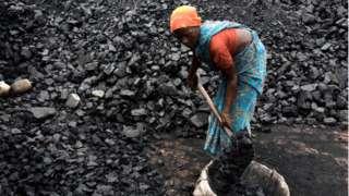 Woman shovels coal in Kamduni brick kiln. Kamduni, West Bengal, India 08.03.17 The brick kilns of Bengal employ a large number of laborers from distant villages of Bihar, Orissa and Uttar Pradesh
