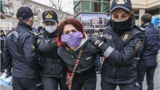 """Две женщины полицейские ведут героиню истории, скрутив ей руки за спиной. На ней медицинская маска с надписью: """"Сражайся как женщина"""""""