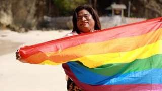 Waria memegang bendera pelangi