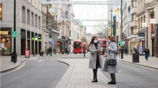 Two people stand in the middle of an empty Oxford Street