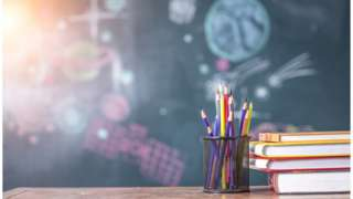 Pencils and a chalkboard in a classroom