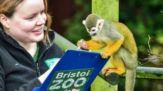 Mammal keeper Olivia Perkins and a squirrel monkey