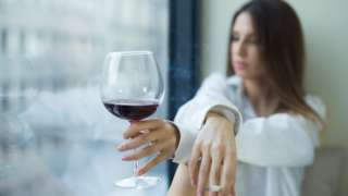 Woman drinking red wine and smoking