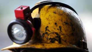 The helmet and lamp of a miner (archive shot)