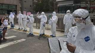 Men in protective clothing conduct coronavirus tests in Beijing