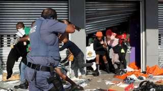 Umupolisi w'Afurika y'epfo agerageza guhagarika imyigaragambyo irimo ubusahuzi mu mujyi wa Durban, ku itariki ya 12 y'ukwa karindwi mu 2021.