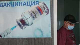 A man walks past a poster for a Russian coronavirus vaccine