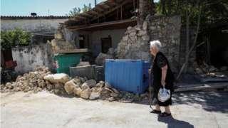 Woman walks near damaged building in Arkalochori, Crete