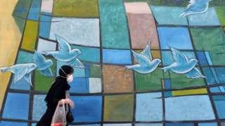 An Iranian women walks past a colourful wall in the capital Tehran
