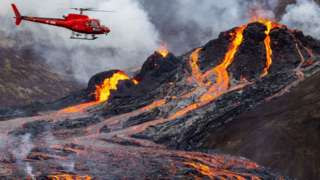 Helicopter near erupting volcano