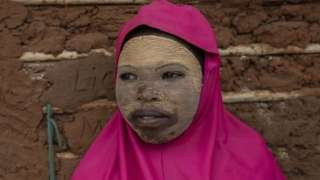 A girl wearing a clay mask and pink scarf smiles.