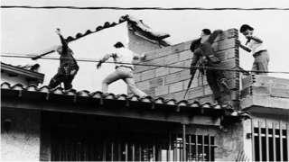 Forças de seguranças colombianas no telhado onde o traficante Pablo Escobar foi morto a tiros em 2 de dezembro de 1993