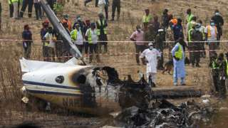 People and rescuers gather at the site where a Nigerian air force plane crashed while approaching the Abuja airport runway, according to the aviation minister, in Abuja, Nigeria February 21, 2021.