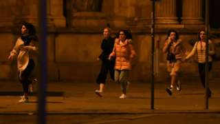 Women run away from the first district near the state opera in central Vienna