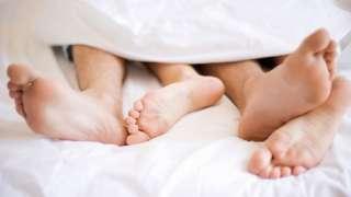 Pies de un hombre y una mujer en la cama