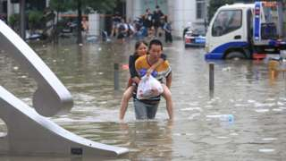 A man carrying a woman wades through a flooded road following heavy rainfall in Zhengzhou