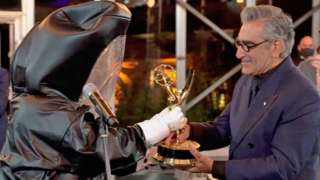 Eugene Levy received his best comedy actor award from a presenter in a hazmat suit