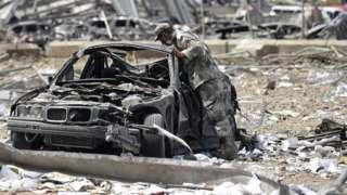 貝魯特港區爆炸現場一名敘利亞士兵查看一輛汽車殘骸(7/8/2020)