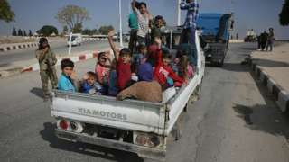 """Civilians are seen on their way to Tal Abyad, part of the """"safe zone"""" on the Syria-Turkey border"""