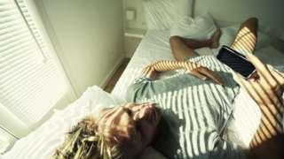 Rapaz deitado na cama olha para a tela do celular
