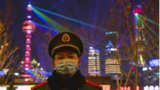 "A member of the PLA guards regulates pedestrians on The Bund waterfront area during New Year""s Eve celebrations in Shanghai, China, 31 December 2020"