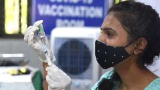 A health worker prepares a dose of Covishield vaccine in Delhi