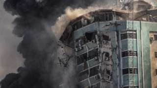 Smoke rises as the Jalaa Tower in Gaza City is destroyed in an Israeli air strike (15 May 2021)