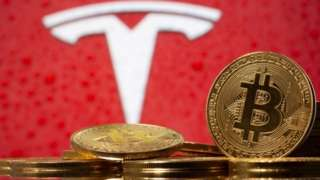 FILE PHOTO: Representations of virtual currency Bitcoin are seen in front of Tesla logo in this illustration taken, February 9, 2021.