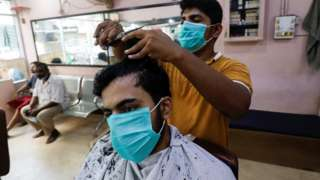 A man wears a protective mask as he has a haircut at a barbershop, after Pakistan lifted lockdown restrictions, as the coronavirus disease (COVID-19) outbreak continues, in Karachi, Pakistan August 10, 2020.