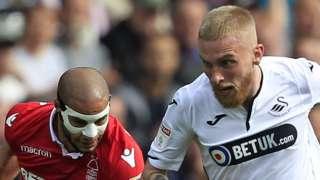 Oli McBurnie of Swansea City (R) runs away from Adlene Guedioura